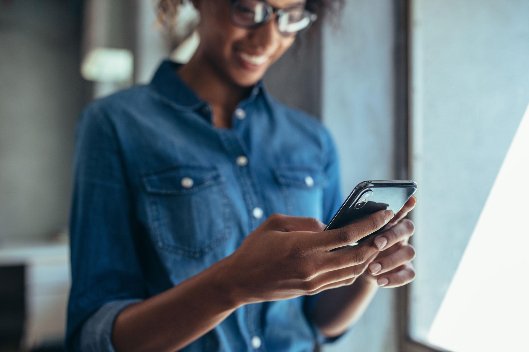 Person ler och tittar i mobiletelefon